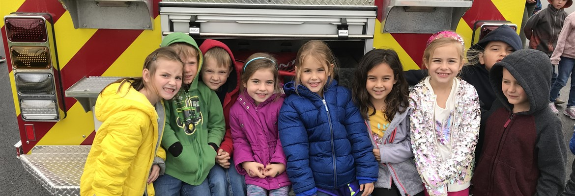 SLES students learning about fire safety. Students sitting on the back of a fire truck.
